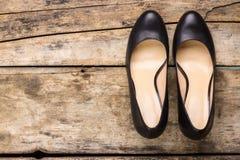 Κλασικά παπούτσια μαύρων γυναικών στο ξύλινο υπόβαθρο Στοκ Εικόνες