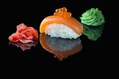 Κλασικά σούσια, πιπερόριζα και wasabi σε ένα μαύρο υπόβαθρο Στοκ Φωτογραφία