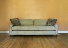 Κλασικός mid-century καναπές ενάντια στον κενό τοίχο Στοκ εικόνα με δικαίωμα ελεύθερης χρήσης