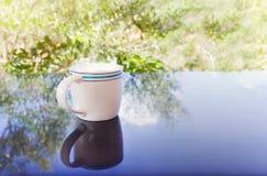 Κλασικό άσπρο φλυτζάνι του μαύρου καφέ που διακοσμείται με το υπόβαθρο λουλουδιών και δέντρων Στοκ εικόνα με δικαίωμα ελεύθερης χρήσης