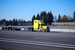 Κλασικό ημι ρυμουλκό κρεβατιών φορτηγών κίτρινο επίπεδο στο διαπολιτειακό αυτοκινητόδρομο Στοκ Φωτογραφία