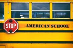 Κλασικό κίτρινο αμερικανικό σχολικό λεωφορείο που μεταφέρει τα παιδιά Στοκ Φωτογραφία
