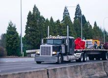 Κλασικό μαύρο ημι φορτηγών μεγάλο εμπορικό φορτίο κρεβατιών εγκαταστάσεων γεώτρησης επίπεδο Στοκ Εικόνα