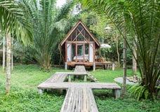 Κλασικό ξύλινο σπίτι ύφους στο εξοχικό σπίτι με την ξύλινη πορεία μπροστά από το σπίτι που περιβάλλεται από τα διάφορα δέντρα άπο Στοκ Εικόνα