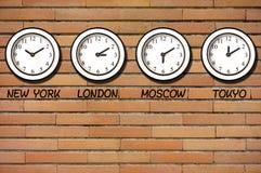 Κλασικό ρολόι Timezone ρολογιών τούβλων τοίχων στοκ εικόνες