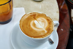 Κλασικό Cappuccino με το σχέδιο φύλλων αφρού γάλακτος σε ένα άσπρο φλυτζάνι επάνω Στοκ φωτογραφίες με δικαίωμα ελεύθερης χρήσης