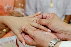 Κλείνω-επάνω στο ταϊλανδικό παραδοσιακό άτομο που βάζει το γαμήλιο δαχτυλίδι στη διαδικασία δέσμευσης στοκ εικόνες