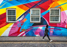 Κλείνω με παντζούρια παράθυρα στον τοίχο που καλύπτεται στην τέχνη οδών ουράνιων τόξων Στοκ φωτογραφία με δικαίωμα ελεύθερης χρήσης