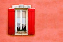 Κλείνω με παντζούρια παράθυρο ενάντια στον κόκκινο τοίχο πετρών Στοκ Φωτογραφίες