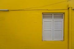 Κλείνω με παντζούρια παράθυρο στον ελάχιστο κίτρινο τοίχο Στοκ εικόνες με δικαίωμα ελεύθερης χρήσης