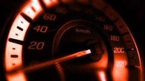 Κλείστε αυξημένος ενός μετρητή ταχύτητας σε ένα αυτοκίνητο με το πορτοκαλί φως στοκ φωτογραφίες