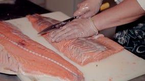 Κλείστε αυξημένος τα κομμένα μάγειρας φρέσκα κόκκινα ψάρια απόθεμα βίντεο