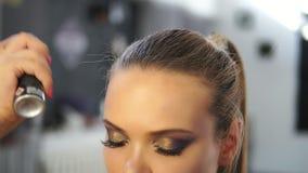 Κλείστε αυξημένος της λακ ψεκασμών hairstylist σε ένα πρότυπο κάνοντας τρίχα- Ο κομμωτής κάνει hairstyle για το πρότυπο απόθεμα βίντεο