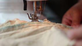 Κλείστε αυξημένος της ράβοντας μηχανής που ράβει ένα ανοικτό καφέ ύφασμα απόθεμα βίντεο