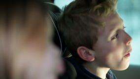 Κλείστε αυξημένος του αγοριού που κάνει τα πρόσωπα στο αυτοκίνητο backseat απόθεμα βίντεο