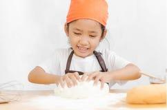 Κλείστε αυξημένος του ασιατικού μικρού κοριτσιού που ζυμώνει τη ζύμη για την παραγωγή στοκ εικόνες