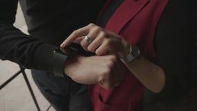 Κλείστε αυξημένος του ατόμου που παρουσιάζει στη φίλη του τα οφέλη των smartwatches στο βραχίονα απόθεμα βίντεο