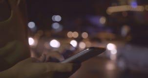 Κλείστε αυξημένος του γραψίματος γυναικών χρησιμοποιώντας τα κινητά τηλέφωνα στο υπόβαθρο bokeh απόθεμα βίντεο