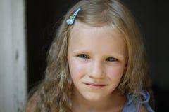 Κλείστε αυξημένος του όμορφου ξανθού μικρού κοριτσιού που φορά το φόρεμα τζιν, εξετάζοντας τη κάμερα στοκ φωτογραφίες με δικαίωμα ελεύθερης χρήσης