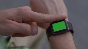 Κλείστε αυξημένος των αρσενικών χεριών που λειτουργούν με τη σύγχρονη συσκευή smartwatch απόθεμα βίντεο