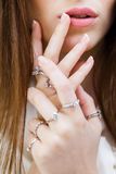 Κλείστε αυξημένος των θηλυκών χεριών με τα δαχτυλίδια στοκ εικόνα