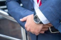 Κλείστε αυξημένος των χεριών επιχειρηματιών με τα watshes στοκ εικόνες
