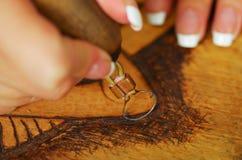 Κλείστε αυξημένος των χεριών το ξύλινο κάψιμο με pyrography τη μάνδρα στοκ εικόνα
