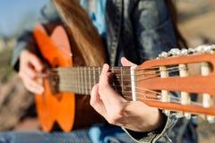 Κλείστε αυξημένος χωρίς πρόσωπο Κιθάρα γυναικών playng η ακτή Στοκ Εικόνες