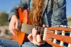 Κλείστε αυξημένος χωρίς πρόσωπο Κιθάρα γυναικών playng η ακτή Στοκ εικόνα με δικαίωμα ελεύθερης χρήσης
