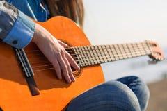 Κλείστε αυξημένος χωρίς πρόσωπο Κιθάρα γυναικών playng η ακτή Στοκ φωτογραφία με δικαίωμα ελεύθερης χρήσης