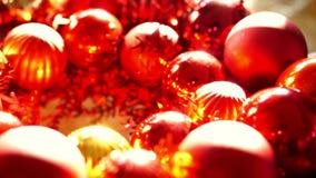 Κλείστε επάνω, λαμπρές κόκκινες και χρυσές διακοσμήσεις σφαιρών Χριστουγέννων στο νέο φως έτους πρωινού φιλμ μικρού μήκους