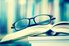 Κλείστε επάνω ανοιγμένα eyeglasses σελίδων και ανάγνωσης βιβλίων με το μουτζουρωμένο β Στοκ φωτογραφία με δικαίωμα ελεύθερης χρήσης