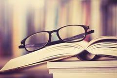 Κλείστε επάνω ανοιγμένα eyeglasses σελίδων και ανάγνωσης βιβλίων με το μουτζουρωμένο β Στοκ Εικόνα