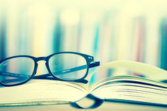 Κλείστε επάνω ανοιγμένα eyeglasses σελίδων και ανάγνωσης βιβλίων με το μουτζουρωμένο β Στοκ Φωτογραφίες