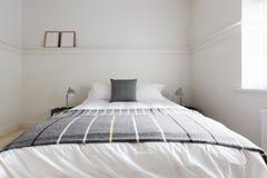Κλείστε επάνω γκρίζου μάλλινου ρίχνει την κουβέρτα στο κρεβάτι φιλοξενουμένων πολυτέλειας Στοκ Φωτογραφίες