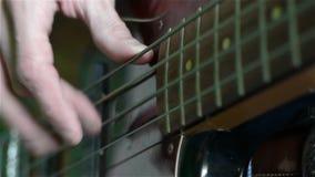 Κλείστε επάνω ενός ατόμου που παίζει μια ηλεκτρική πέρκα κιθάρων απόθεμα βίντεο