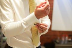 Κλείστε επάνω ενός ατόμου χεριών πώς φορά το άσπρα πουκάμισο και το μανικετόκουμπο Στοκ φωτογραφία με δικαίωμα ελεύθερης χρήσης
