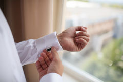 Κλείστε επάνω ενός ατόμου χεριών πώς φορά το άσπρα πουκάμισο και το μανικετόκουμπο στοκ εικόνες