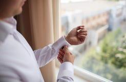 Κλείστε επάνω ενός ατόμου χεριών πώς φορά το άσπρα πουκάμισο και το μανικετόκουμπο στοκ φωτογραφία
