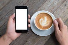 Κλείστε επάνω ενός ατόμου χρησιμοποιώντας το έξυπνο τηλέφωνο με κενό κινητό και το φλυτζάνι Στοκ Εικόνες