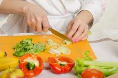 Κλείστε επάνω ενός θηλυκού χεριού που το τέμνον σέλινο, βρίσκεται γύρω από τα λαχανικά και τα φρούτα Στοκ Εικόνες