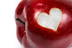 Κλείστε επάνω ενός κοκκίνου - εύγευστο μήλο με μια καρδιά διακοπής Στοκ Φωτογραφία