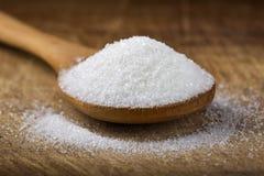 Κλείστε επάνω ενός κουταλιού μπαμπού που γεμίζουν με την άσπρη ζάχαρη στο ξύλο Στοκ Εικόνες