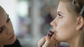 Κλείστε επάνω ενός προσώπου του νέου θηλυκού photomodel κατά τη διάρκεια της διαδικασίας σύνθεσης στο κατάστημα ομορφιάς Το επαγγ φιλμ μικρού μήκους