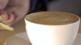 Κλείστε επάνω ενός φλιτζανιού του καφέ στο οποίο αναμιγνύοντας το νόστιμο αφρό αργά φιλμ μικρού μήκους