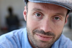 Κλείστε επάνω ενός χαμογελώντας ατόμου στο καπέλο πωλητών εφημερίδων που κοιτάζει στη κάμερα Στοκ Εικόνες