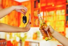 Κλείστε επάνω ενός χεριού κρατώντας ότι ένα αυτοκίνητο κλειδώνει την άρνηση μιας μπύρας από ένα άλλο χέρι που κρατά, στο υπόβαθρο Στοκ εικόνες με δικαίωμα ελεύθερης χρήσης