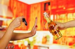 Κλείστε επάνω ενός χεριού κρατώντας ότι ένα αυτοκίνητο κλειδώνει την άρνηση μιας μπύρας από ένα άλλο χέρι που κρατά, στο υπόβαθρο Στοκ Εικόνες