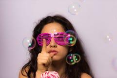 Κλείστε επάνω ενός όμορφου κοριτσιού με τις επαγγελματικές φυσαλίδες σαπουνιών σύνθεσης φυσώντας γύρω από την Στοκ φωτογραφία με δικαίωμα ελεύθερης χρήσης