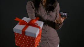 Κλείστε επάνω με τα χέρια γυναικών που κρατούν τα μεγάλα και μικρά κιβώτια δώρων και που παρουσιάζουν τα ως εναλλακτική λύση φιλμ μικρού μήκους